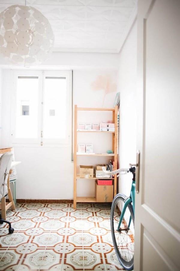 despacho con estantería, tabla con caballetes por mesa, puertas pintadas y bicicleta