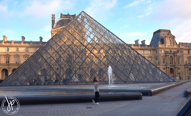 louvre pyramid, woman walking