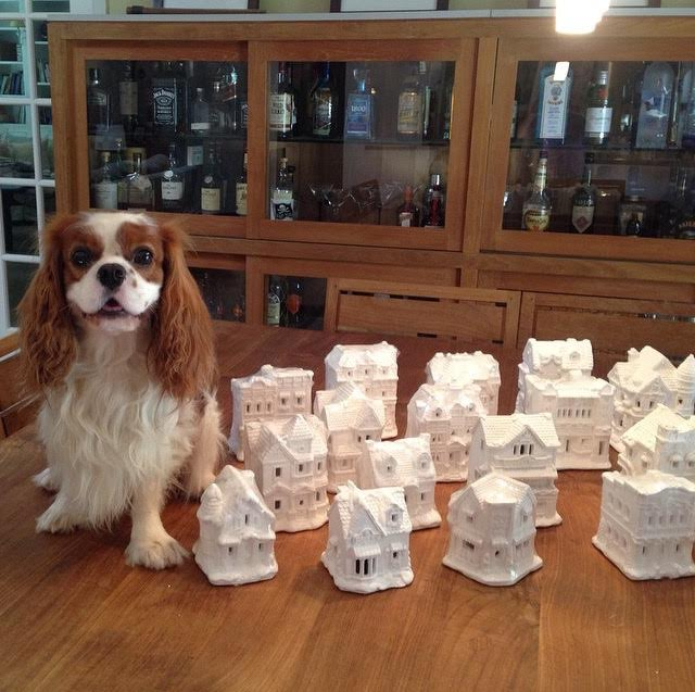 Blenheim Cavalier King Charles Spaniel sitting by unpainted Christmas Village