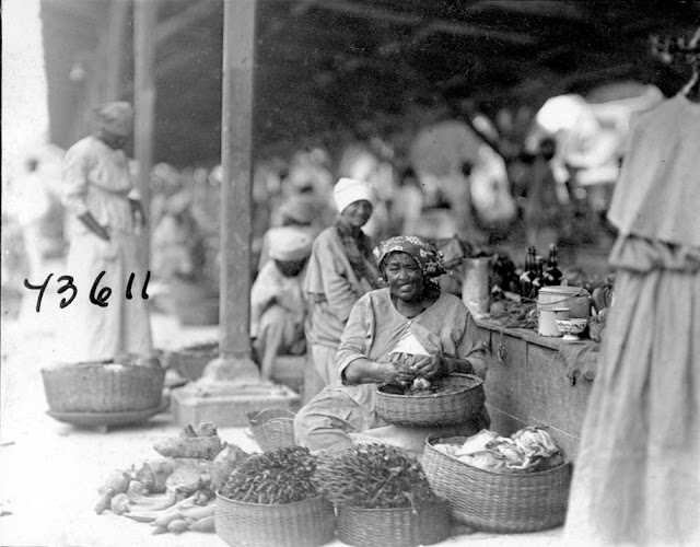 Market scene in Paramaribo. Fruit of Elaeis guineensis Palmae (oil palm) in baskets. Plant Industry. 1922. Paramaribo, Guyana, South America