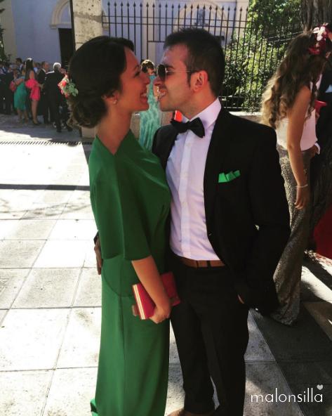 Pareja de invitados a boda, ella con vestido verde esmeralda largo, bolso tipo clutch en fucsia y tocado de flores tipo peineta en verde esmeralda y fucsia buganvilla by Malonsilla