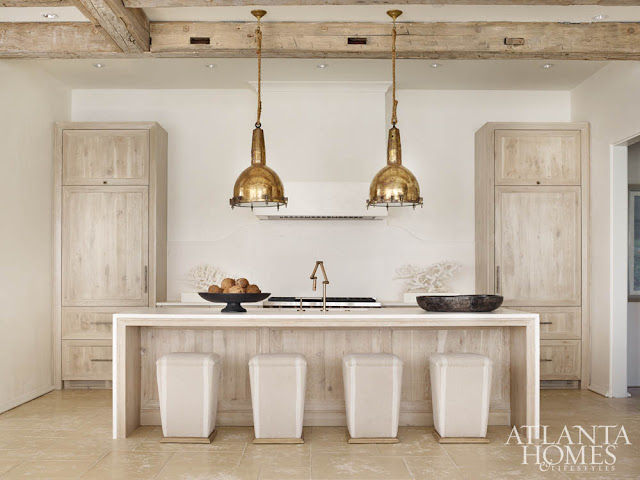 Warm and modern minimal design in kitchen with oversized brass pendants