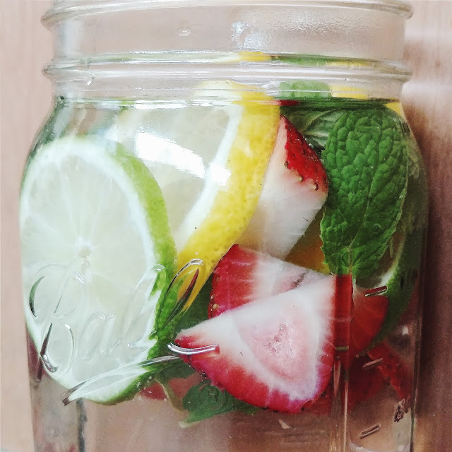 Mason jar filled with water and infused with lemon, lime, strawberry, and mint.