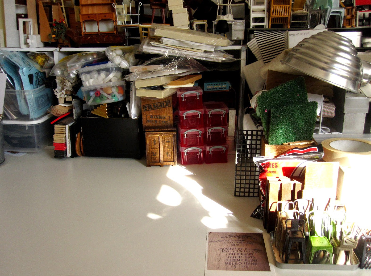 Work table with piles of dolls' house miniature furniture and supplies and a clear space in the middle.