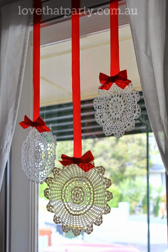 hanging vintage fabric doilies with red ribbon at Christmas