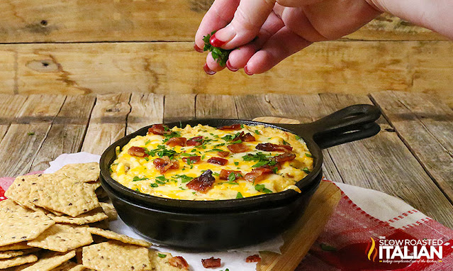 skillet of baked jalapeno popper dip surround by multigrain crackers