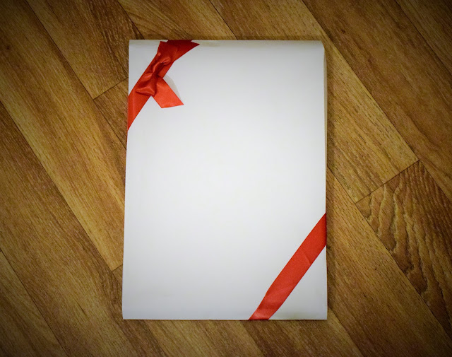 A white envelope with a simple red ribbon.