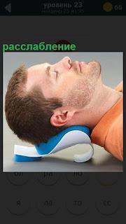 Мужчина головой лежит на специальной подушке, расслабление мышц тела