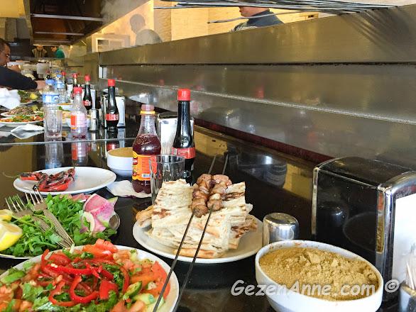 ciğer ekmekleri üzerinde yenilmeye bekleyen ciğerler, yanında yeşillikler ve şalgam, Birbiçer Adana