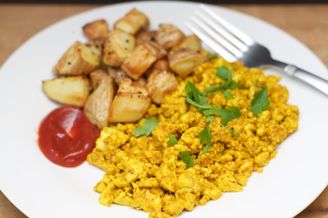 The finished tofu scramble, on a plate, with roasted potatoes and ketchup.