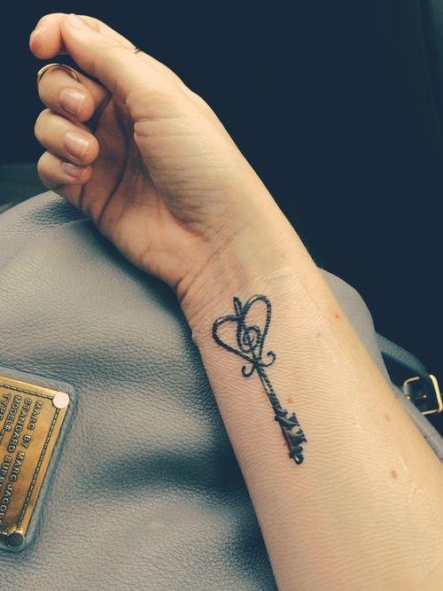 Chica nos enseña su antebrazo lleva el tatuaje de una llave antigua