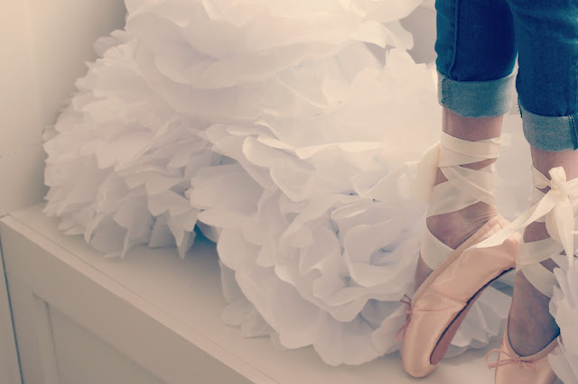 Beautiful soft feminine dancer in pointe shoes with white tissue pouf blooms