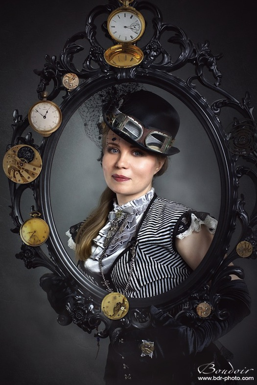 Steampunk woman in burlesque clothing in satin and black and white stripes, with hat goggles, and steampunk picture frame