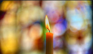 A lit candle, against a background of coloured glass in a cathedral