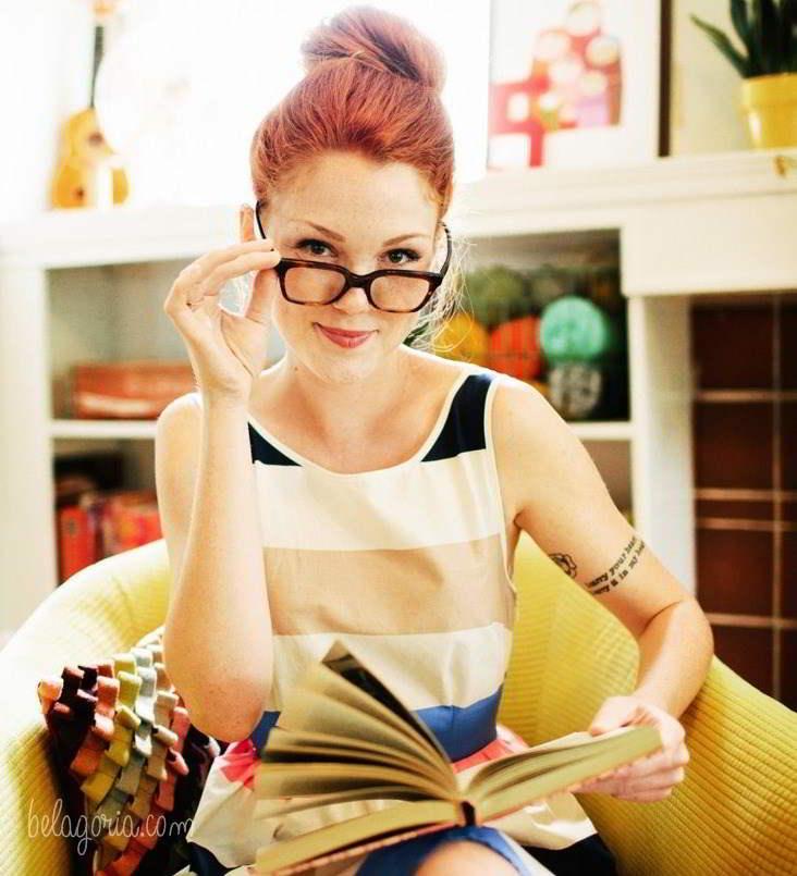 Preciosa mujer peliroja subiendose las gafas, lleva tatuaje de brazalete de letras