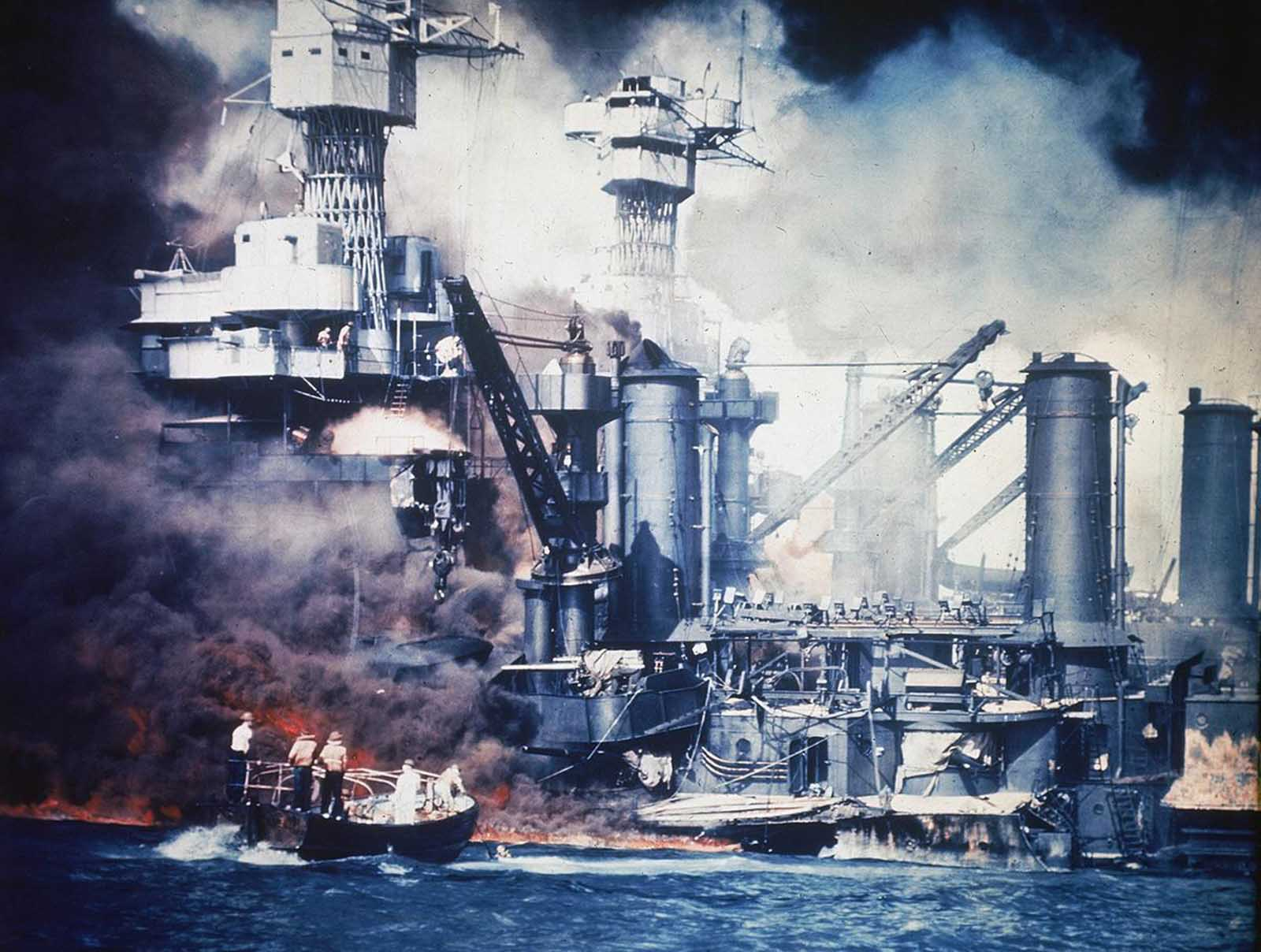 A small boat rescues a USS West Virginia crew member from the water after the Japanese bombing of Pearl Harbor, Hawaii, on December 7, 1941. Two men can be seen on the superstructure, upper center. The mast of the USS Tennessee is beyond the burning West Virginia.