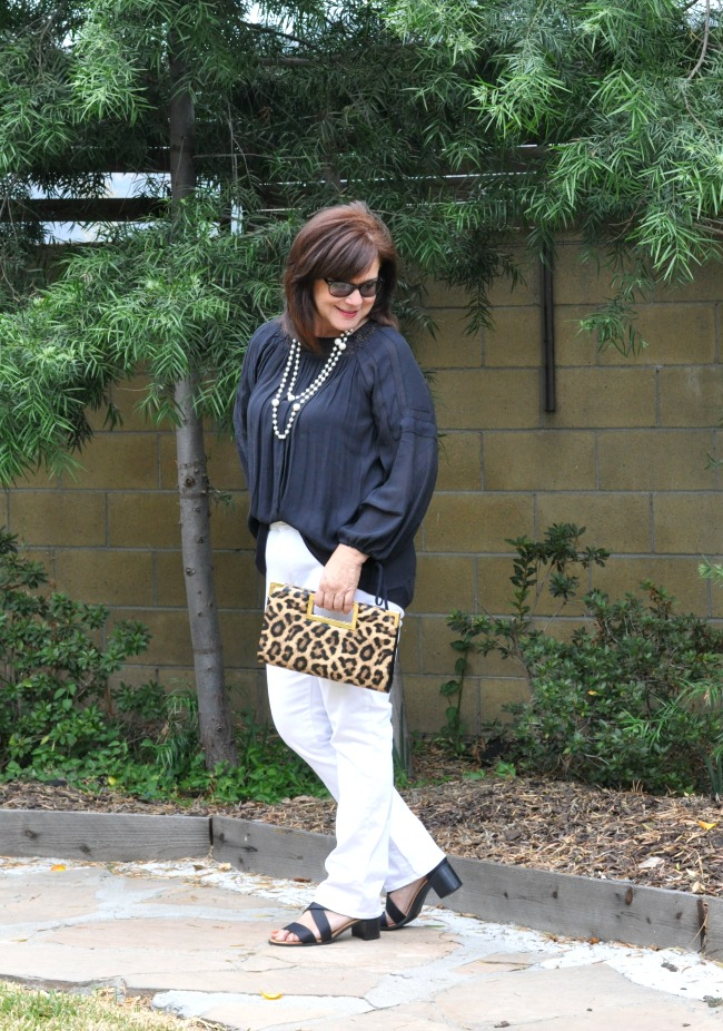 black top white jeans and leopard clutch