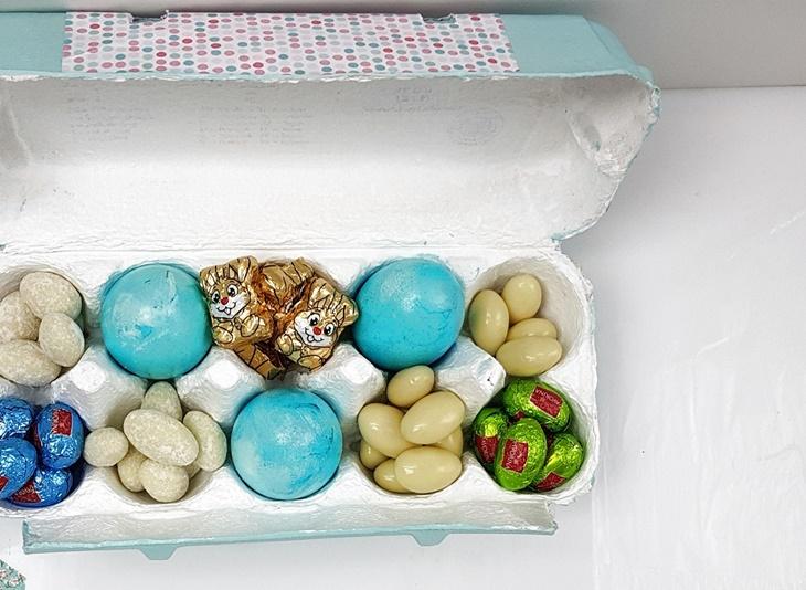 blau bemalter Eierkarton mit Ostereiern und Osterhasen