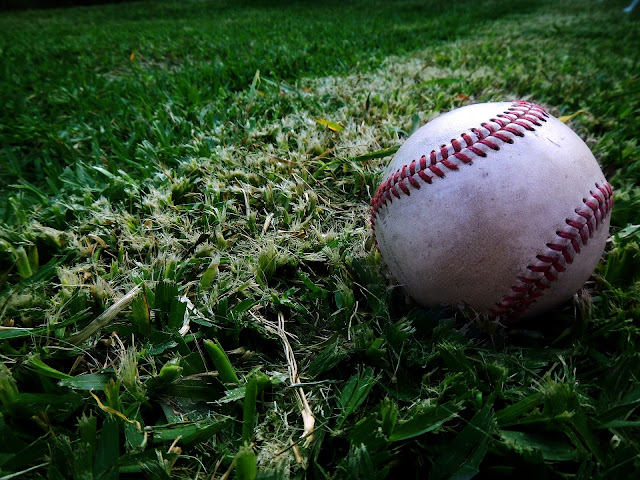 A baseball laying on top of turf.