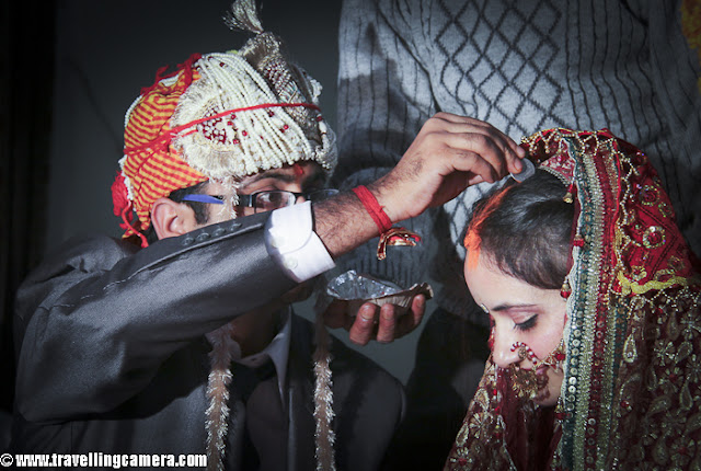 Var Mala ceremony is an important main wedding day ceremony. It is also known as Jaimala and basically involves exchange of garlands between the bride and the groom. Like all other customs and rituals, this is also a significant ceremony which finds reference even in the Vedic literature. It is an ancient practice and is still observed in India. fter Varmala Ceremony, both of the main parties need to sit on hot seats to have good wishes of their relatives and loved ones !!!And of course, need to practice a smile which comes consistently with each photograph of relatives behind these seats...Friends plays important role in a marriage and is a good support when you have handle with bride's sisters/friends :)SaptapadiOne of the most significant rituals the bride and the groom perform is the Saptapadi or saat phere around a scared fire that is symbolic of God. One end of the groom's scarf is tied to the bride's dress and this marriage knot is supposed to symbolize a life-long togetherness. Then they take seven rounds around the fire and each of these rounds represents nourishment, strength, prosperity, happiness, progeny, long life and harmony and understanding, respectively. It is also during this time that the groom fills vermillion or sindoor in the center parting of the bride and puts mangalsutra around her neck.This process of adding vermillion or sindoor takes place thrice and of course it's very difficult to control the amount of sindur being placed each time... Gorgeous smile after one of the main ceremony of Himachali Marriage - Sindoor !!
