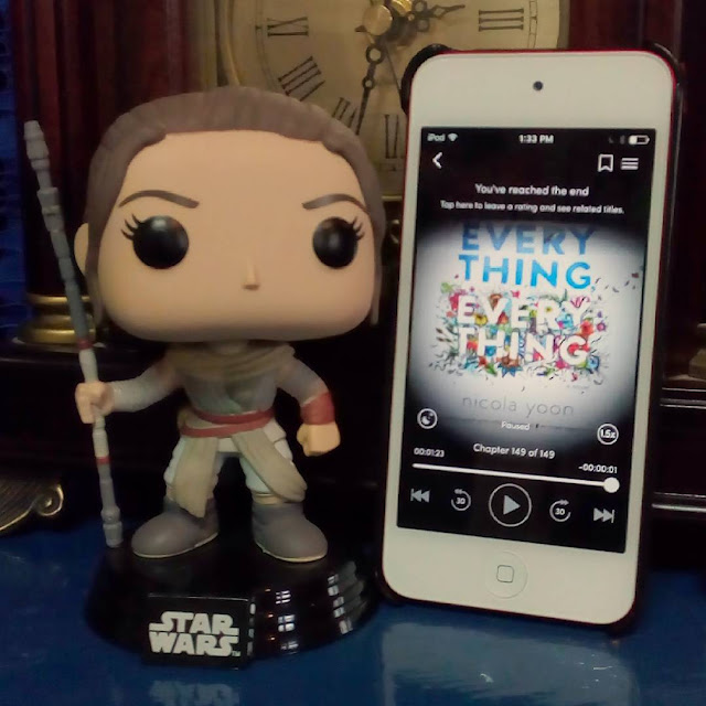 A large-headed Funko Pop bobblehead of Rey from Star Wars stands beside a white iPod with the cover of Everything, Everything on its screen. The cover is mostly white, with the first word in sky blue and the second in white outlined by colourful creepy crawlies.