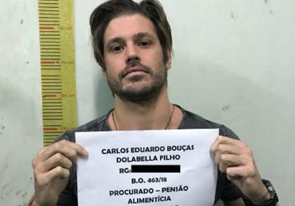 Ator Dado Dolabella Segurando plaquinha com seu nome indentificando-o preso