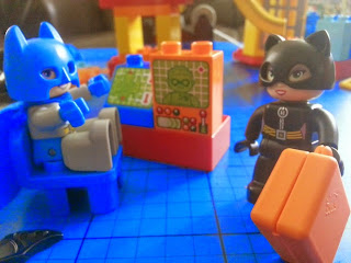 Batman sits at his computer and Catwoman walks past carrying a suitcase