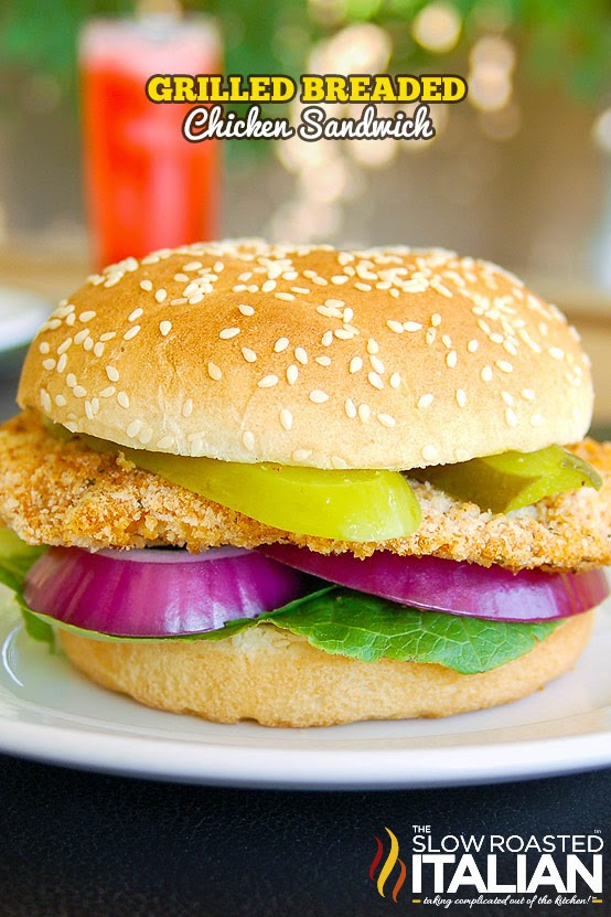 Grilled Breaded Chicken Sandwich topped with pickles and red onion, on white plate