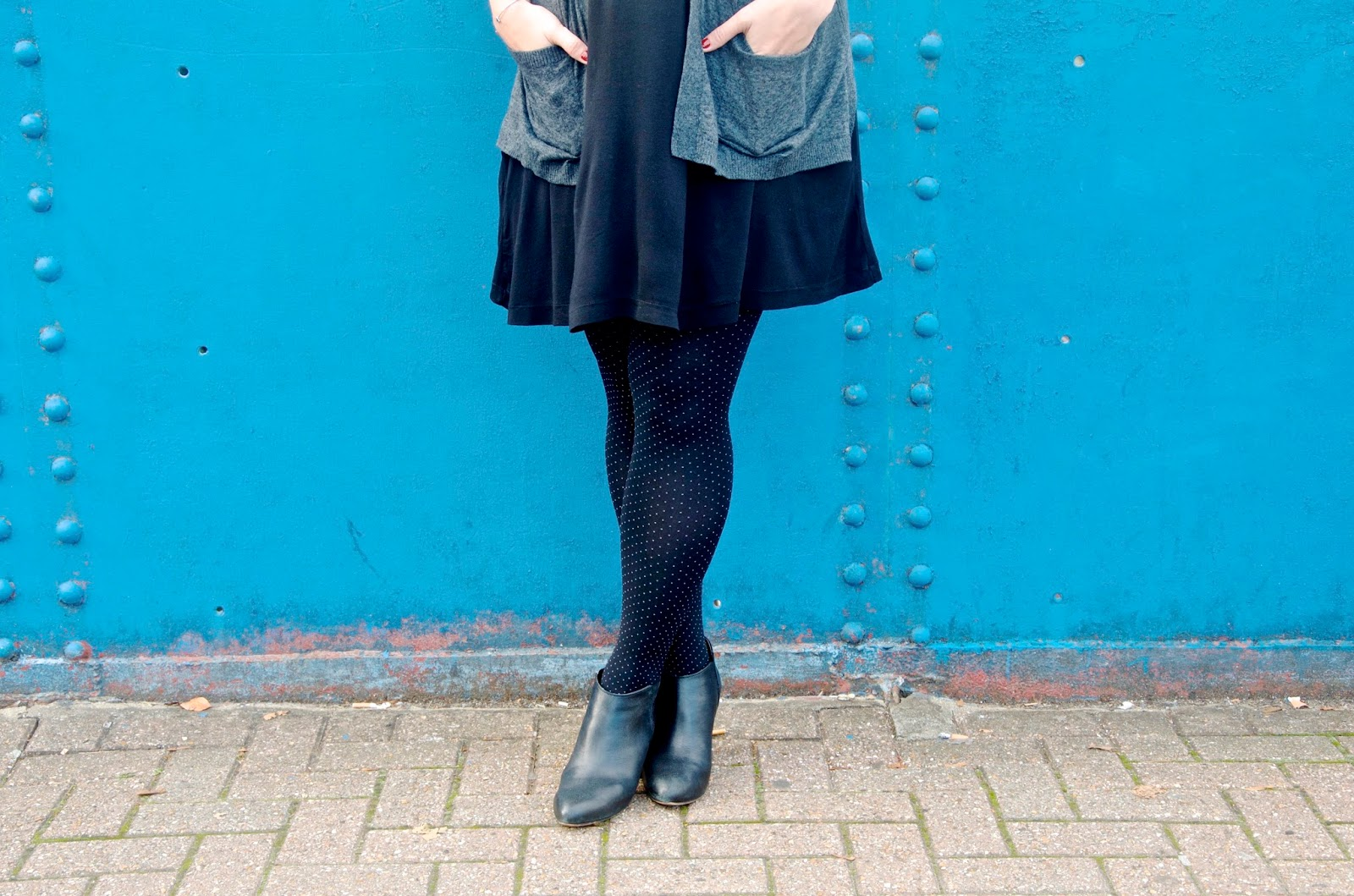 Short black dress, polka dot tights, black shoes, grey cardigan, blue wall