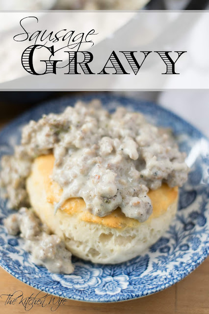 A blue plate with a biscuit on it smothered in the sausage gravy.