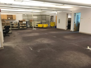 Large empty room with a few desks and carts around side