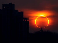2012 annular solar eclipse seen at sunset near buildings