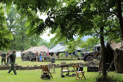 Vietnam era military encampment with tents and jeep, people in uniform