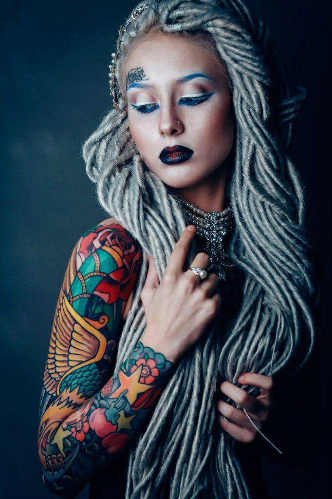 chica con el pelo de lana, lleva tatuaje de aguila a color en el brazo