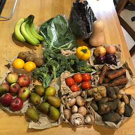A selection of fruit and vegetables laid out: two bags of leaves, a butternut squash, onions, pepper, broccoli, tomatoes, carrotsm potatoes, mushrooms, apples, pears, oranges, kiwis and bananas.