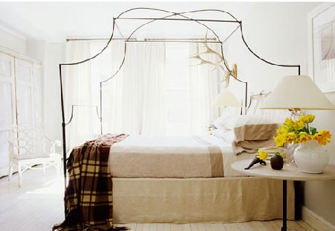 modern rustic bedroom with canopy bed, wood floors, a plaid throw and white floor length curtains