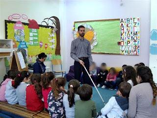 Ο Βαγγέλης δείχνει στα παιδιά πως χρησιμοποιεί το λευκό μπαστούνι