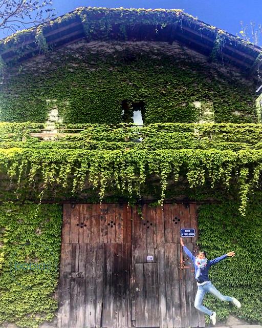 femme qui saute de joie devant une maison recouverte de lierre à Axat