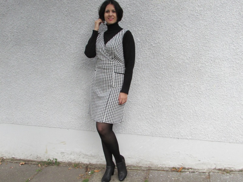 Pinafore dress layered over a roll neck sweater  dress