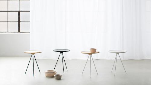 Mehrere Tische mit drei Beinen stehen nebeneinander vor einem Fenster.