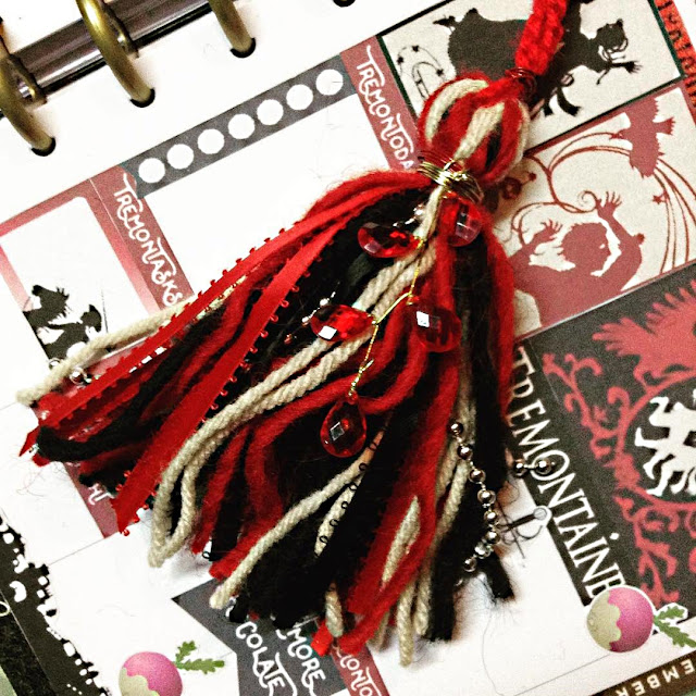 A yarn and ribbon tassel in shades of red, black, and beige. The tassel is bound in gold wire and has a branch of faceted red plastic jewels attached to gold wire descending from it.