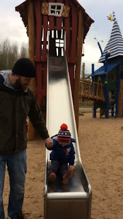 Little boy on a slide being helped by his Daddy