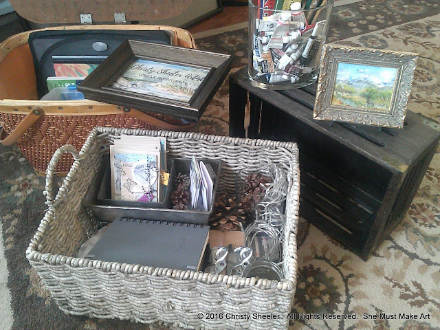 Gathering beautiful items for display table.  Baskets and crates with pine cones and strings of lights.