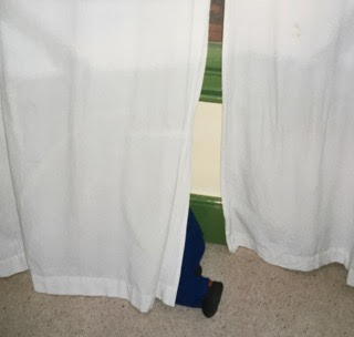 A Small Child Hides Behind a White Curtain