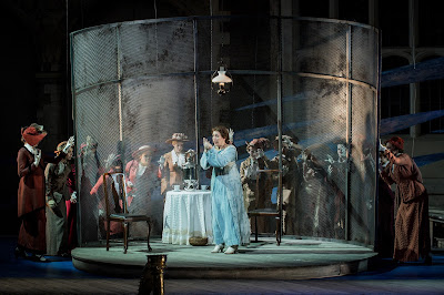 Julia Sporsén as Káťa and members of the OHP Chorus in Opera Holland Park's production of Káťa Kabanová, directed by Olivia Fuchs © Robert Workman