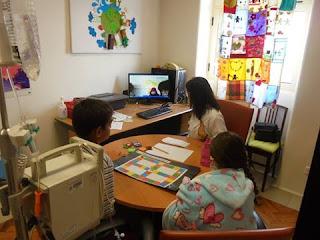 Alunos e professora a olhar para ecrã (TeleAula - sessão de videoconferência)
