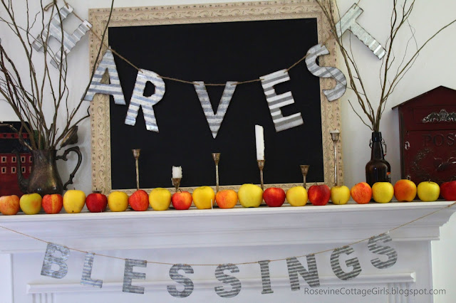 Minimalist Farmhouse Apple Mantel | photo of mantel decorated for fall with black chalkboard, willow branches, red and yellow apples, a red barn and red antique mailbox