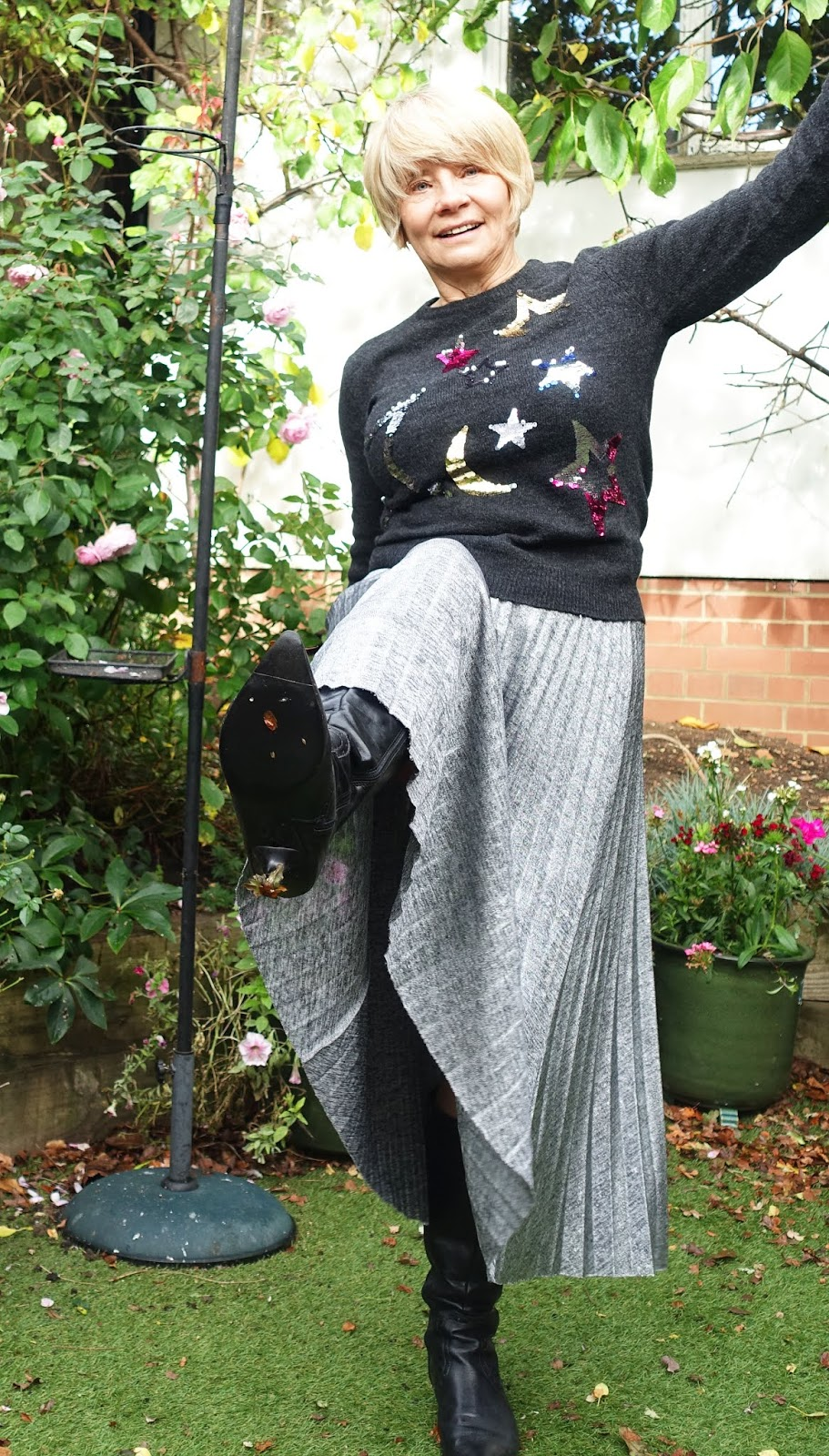 A high kicking blogger shows off a David Bowie post in a sequinned stars sweater and silver pleated skirt