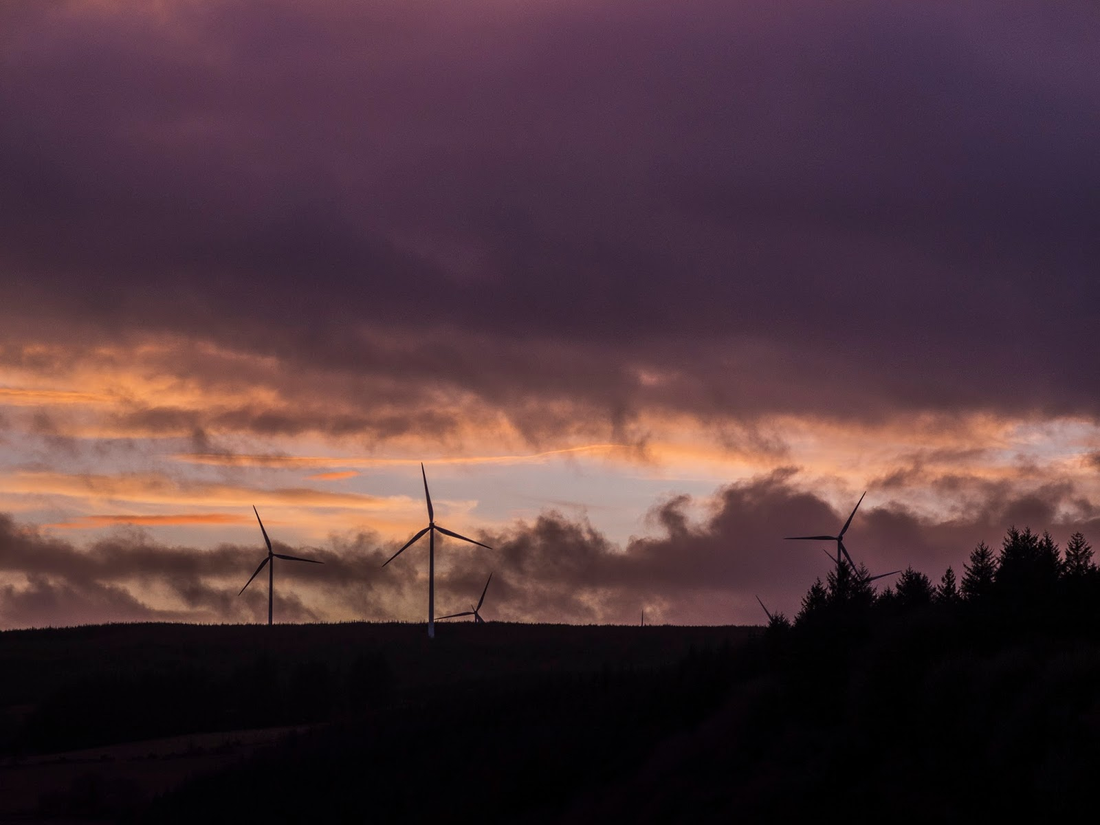 Windmills on a hill in the Boggeragh Mountains in North Cork with dramatic sunset clouds.