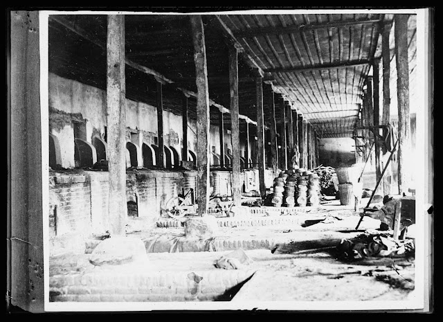 Part of the huge bakery at Monastir turned over to the A.R.C. by the French Army. If formerly supplied the Allied Army of the Orient with 125,000 loaves of bread a day. Now it is sued to help feed the starving civilian population in this district of the Balkans. The baskets heaped in the background are used to hold the kneaded dough, which is placed in the pits drawing heat from the fire-boxes, to rise. The fires are raked out and the dough is put into the fire-boxes on long planks being baked by the heat retained in the sontes. Each loaf baked here weighs three pounds and is in the shape of a fair-sized dish-pan. A mill where wheat is ground into flour adjoins the bakery and is operated by the A.R.C.